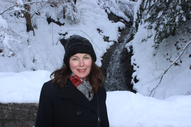 Mom smiling before a jerk threw a snowball up into a tree above us, thereby dumping cold, wet snow all over us.