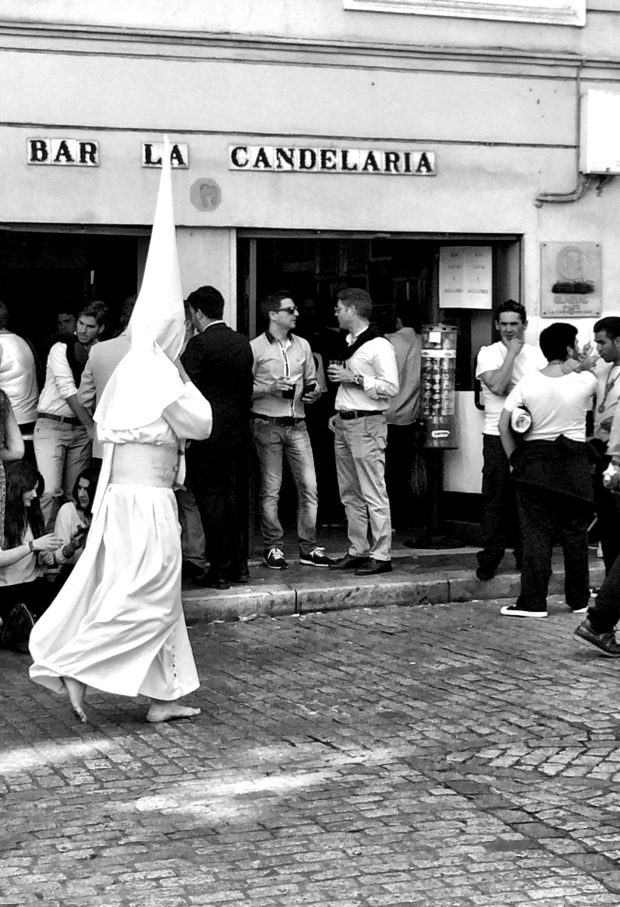A barefoot Nazareno passes a bar full of Costalero's on break (the men who carry the floats).